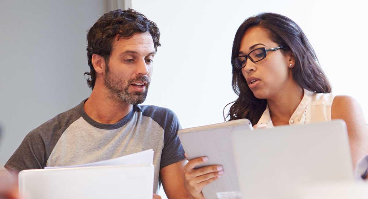 Zwei Übersetzer besprechen zu übersetzende Dokumente